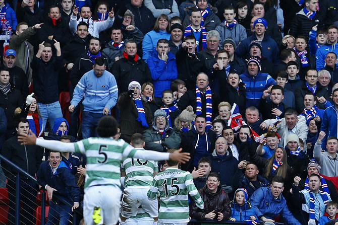 Celtic players celebrate Griffiths' goal in front of Rangers fans during their Scottish League Cup semi final matchin Glasgow, Scotland