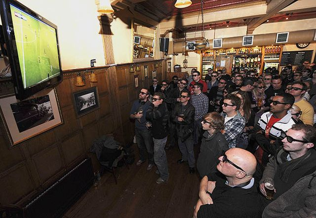 Football fans watch a live 3D TV football match in a pub in London