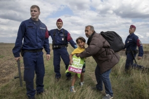 1442827203_migrant-carrying-child-falls-after-tripping-tv-camerawoman-r-while-trying-escape